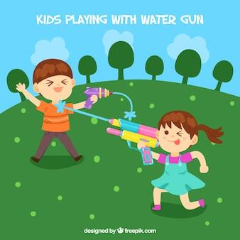 Dzieci bawiące się w parku z plastikowymi pistoletami na wodę