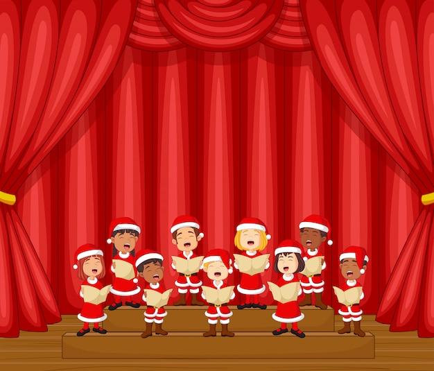 Dzieci chóru śpiewają piosenkę na scenie z kostiumem świętego mikołaja