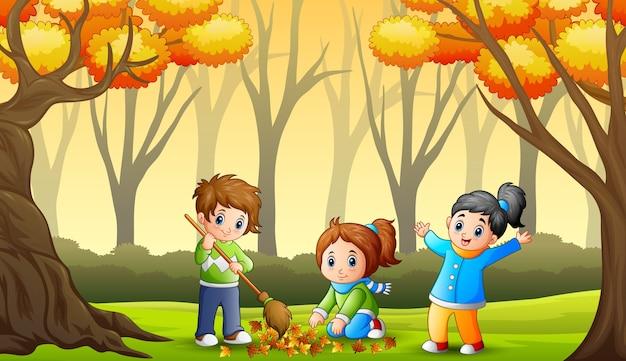Dzieci czyszczą opadłe liście w ogrodzie