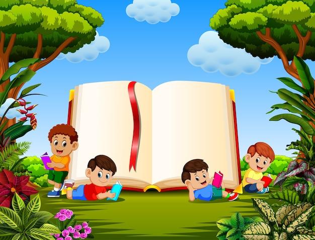 Dzieci czytają książkę w różnych pozujących z dużą książką w ogrodzie