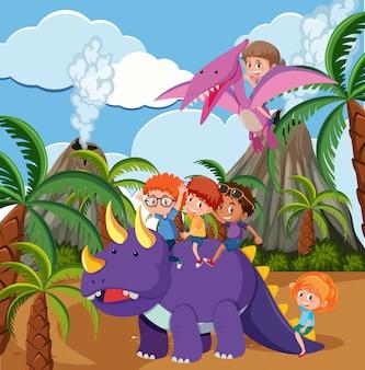 Dzieci jadące dinozaurami w prehistorycznej scenie