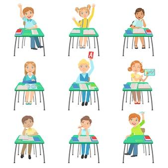 Dzieci siedzą przy biurkach szkolnych w klasie