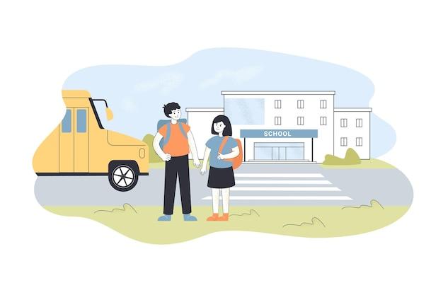 Dzieci stojące na zewnątrz szkolnego dziedzińca. kreskówka chłopiec i dziewczynka w pobliżu wejścia do szkoły, autobusu i drogi w tle płaskiej ilustracji