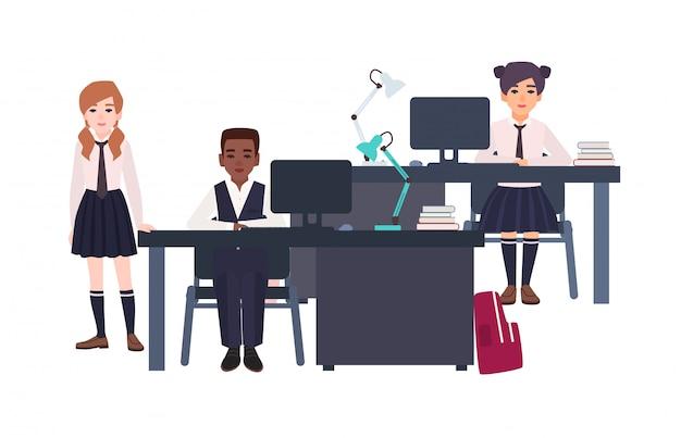 Dzieci ubrane w mundurki szkolne siedzą przy biurkach z komputerami