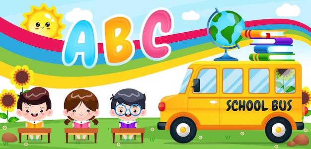 Dzieci uczące się w ogrodzie z banerem szkolnego autobusu