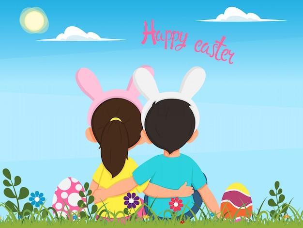 Dzieci w kostiumach królików siedzą na trawie wśród pisanek i patrzą w piękne wiosenne niebo.
