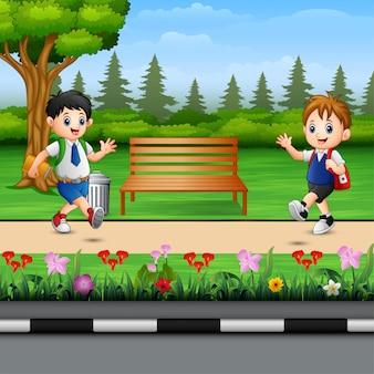 Dzieci w mundurach biegną na drodze parkowej