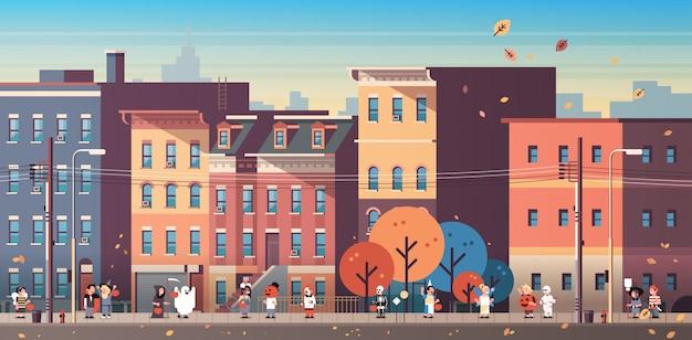 Dzieci w strojach potworów chodzenie w tle miasta