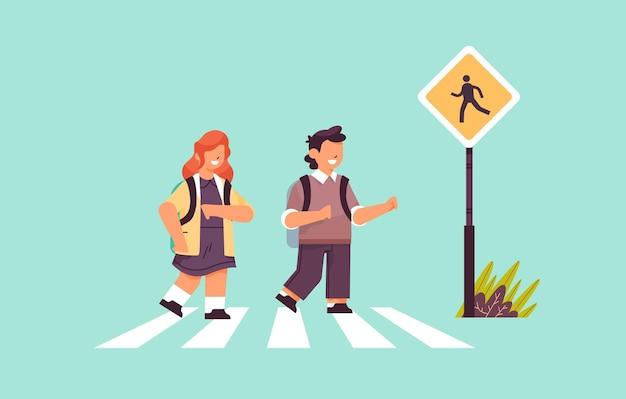 Dzieci w wieku szkolnym przechodzące przez ulicę na przejściu dla pieszych z szyldem bezpieczeństwa na drodze
