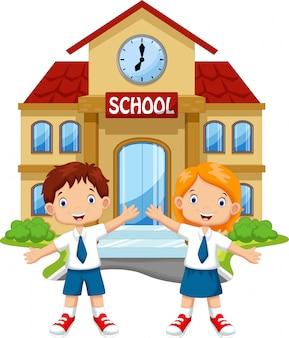 Dzieci w wieku szkolnym przed budynkiem szkoły