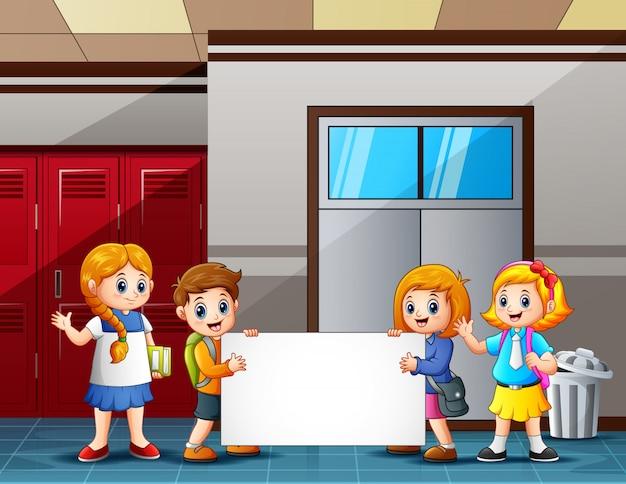 Dzieci w wieku szkolnym trzyma pusty znak przed klasą