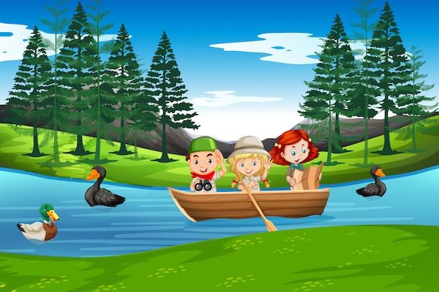 Dzieci wiosłują na drewnianej łodzi