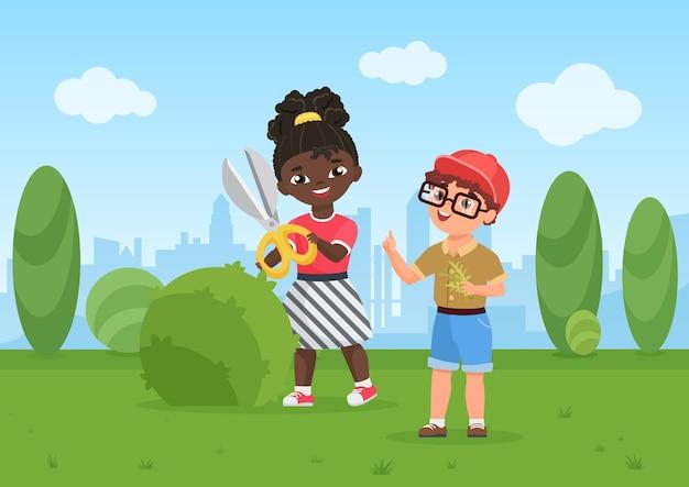 Dzieci wycinają zielony krzew ogrodnik dzieci wykonują prace ogrodowe przedszkole chłopiec dziewczyna ogrodnictwo