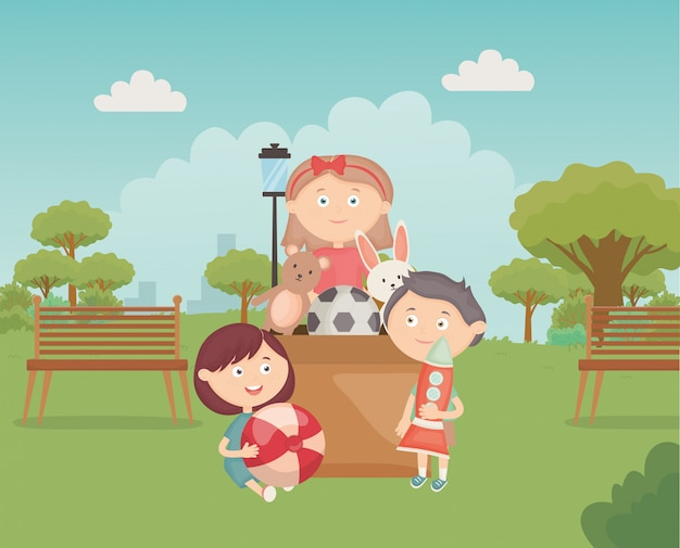Dzieci z kartonem pełne zabawek w parku