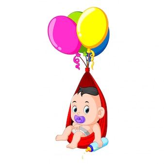 Dziecko cieszy się pod balonem trzymając smoczek