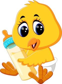 Dziecko kurczaka trzyma butelkę mleka