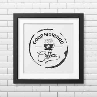 Dzień dobry, pij kawę - cytat typograficzne tło w realistycznej kwadratowej czarnej ramce na ścianie z cegły