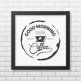 Dzień dobry, pij kawę - typograficzny cytat w realistycznej kwadratowej czarnej ramce na ścianie z cegły.
