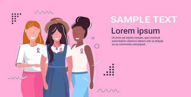 Dzień raka piersi mieszanka wyścigu kobiety noszące ubrania z różową wstążką stojące razem, świadomość choroby i profilaktyka