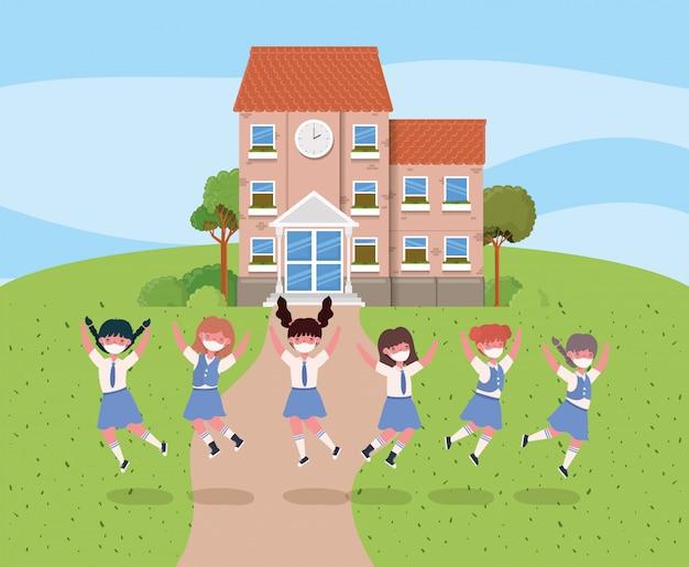 Dziewczęta dzieci w maskach skaczących przed szkołą