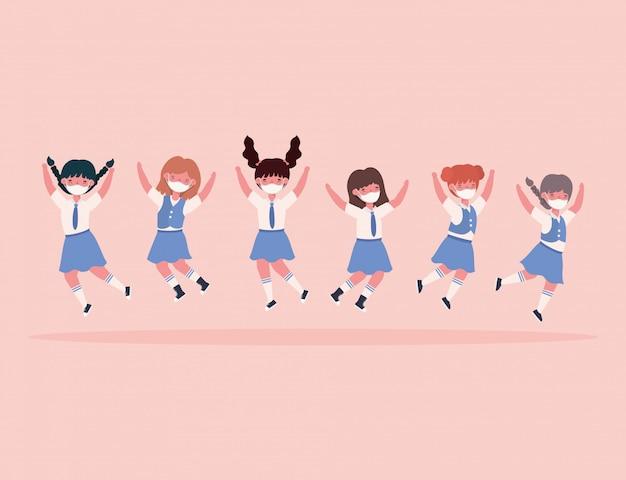 Dziewczęta dzieci z mundurami i masek medycznych skoki