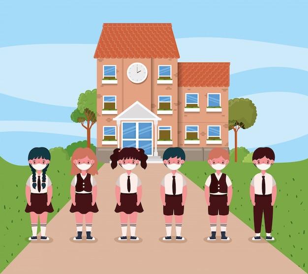 Dziewczęta i chłopcy dzieci z maskami przed szkołą