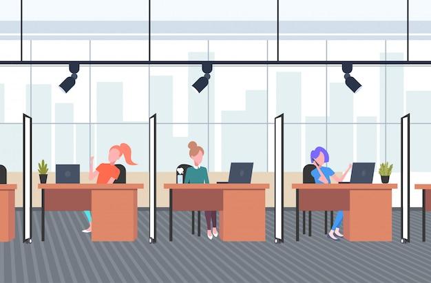 Dziewczęta współpracownicy w kreatywnym biurze kobiety operatorzy siedzący przy biurku biurka call center koncepcja współpracujący otwarta przestrzeń wewnętrzna pozioma pełna długość