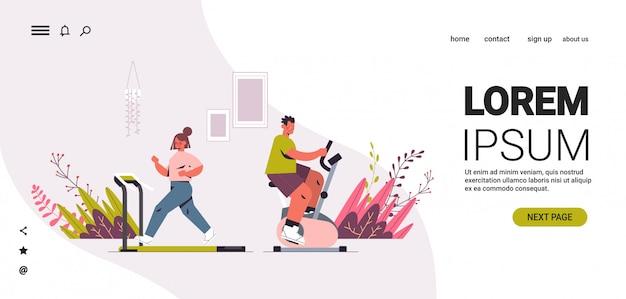 Dziewczyna biega na bieżni mężczyzna jedzie na rowerze stacjonarnym para ma trening cardio fitness trening zdrowy styl życia dom sport koncepcja pozioma kopia przestrzeń pełna długość ilustracja