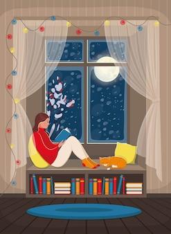 Dziewczyna czytająca książkę na parapecie. przytulne wnętrze ze śnieżnym oknem, regałem i kotem.