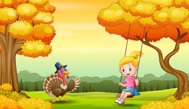 Dziewczyna gra huśtawki w jesiennym krajobrazie