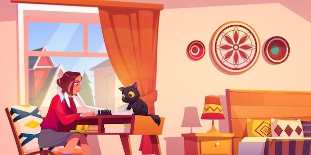 Dziewczyna gra w szachy ze śmiesznym kotem w swojej sypialni młoda kobieta gra planszowa rekreacja przygotow...