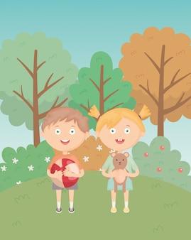 Dziewczyna i chłopak z piłką i misiem w parku trawy, zabawki dla dzieci