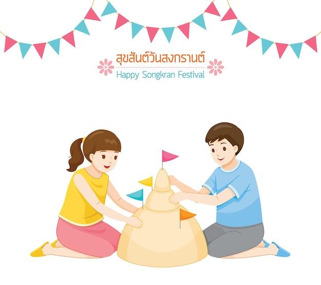 Dziewczyna i chłopiec budują razem pagodę z piasku tradycja tajski nowy rok suk san wan songkran przetłumacz happy songkran festival