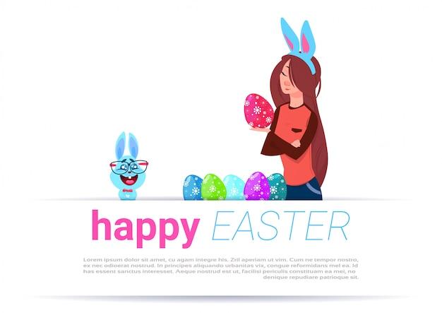 Dziewczyna jest ubranym królików ucho maluje jajka nad szczęśliwym wielkanocnym szablonu tłem z śmiesznym królikiem