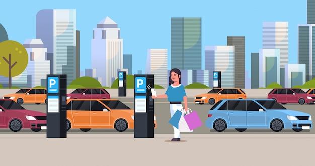 Dziewczyna kierowca płaci do miejsca parkingowego przez smartfona na stacji płatnej biletomat maszyny nfc system płatności koncepcja nowoczesny gród tło płaskie pełnej długości poziome