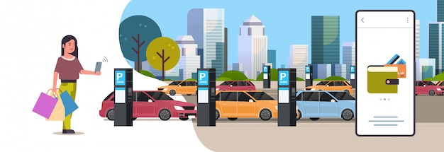 Dziewczyna kierowca płaci parkowanie miejsce parking przy telefonem stacja biletowa system płatności pojęcie mobilny portfel nowożytny pejzaż miejski mieszkanie pełna długość