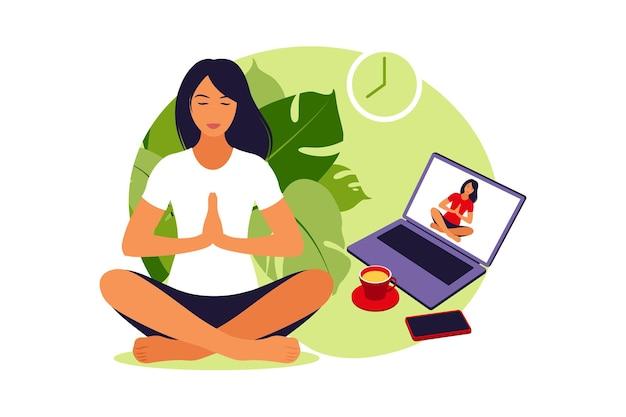 Dziewczyna ogląda zajęcia online na laptopie, praktykuje jogę, medytację. koncepcja medytacji, relaks, rekreacja, zdrowy styl życia, joga. kobieta w pozycji lotosu.