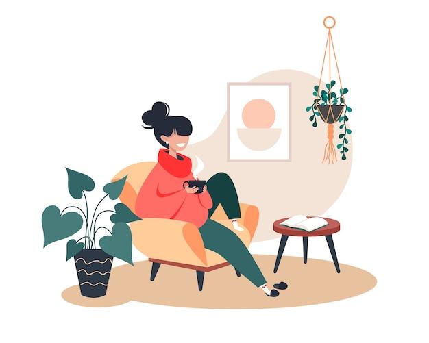 Dziewczyna pije gorącą herbatę siedząc w fotelu, zostań w domu, przytulne wnętrze pokoju