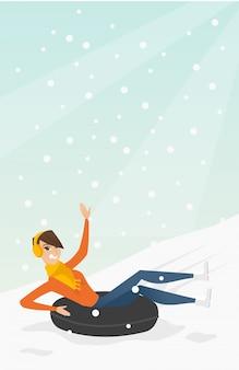 Dziewczyna sankach na śniegu gumowej tubie w górach