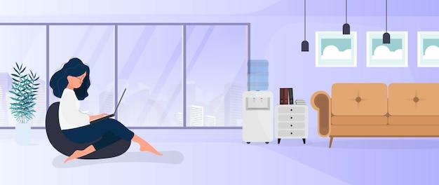 Dziewczyna siedzi na podnóżku i pracuje przy laptopie. kobieta z laptopem siedzi na dużej pufie. koncepcja wygodnej pracy w biurze lub w domu. wektor.