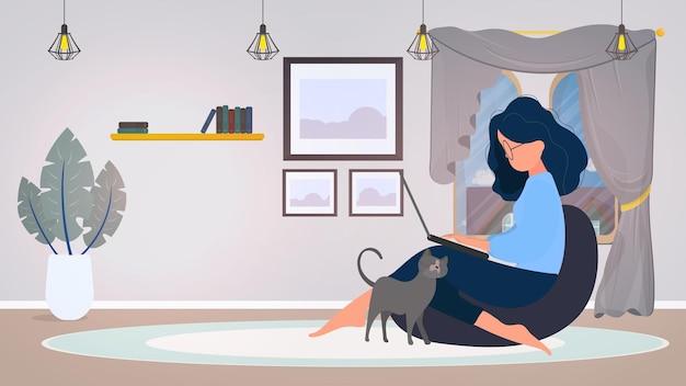 Dziewczyna siedzi na podnóżku i pracuje przy laptopie. kobieta z laptopem siedzi na dużej pufie. kot ociera się o nogę dziewczyny. koncepcja wygodnej pracy w biurze lub w domu. wektor.