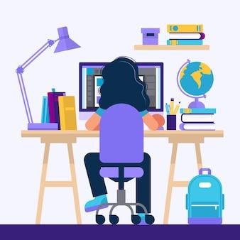 Dziewczyna siedzi przy biurku, uczy się z komputerem.
