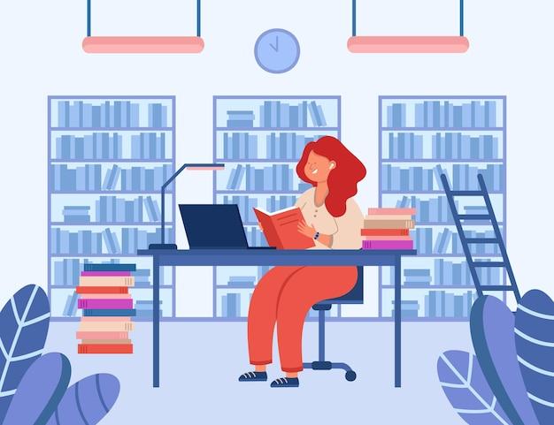Dziewczyna siedzi przy biurku w bibliotece i czytanie książki. wesoła pani studiuje, patrząc na ekran laptopa. półki z książkami w tle. edukacja, koncepcja wiedzy
