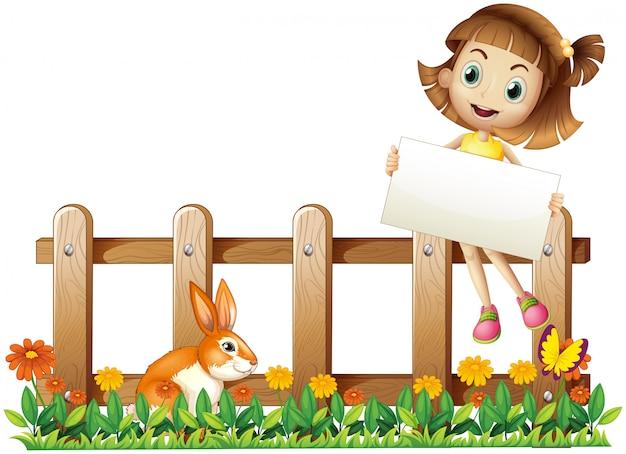 Dziewczyna siedzi przy ogrodzeniu z pustą deską