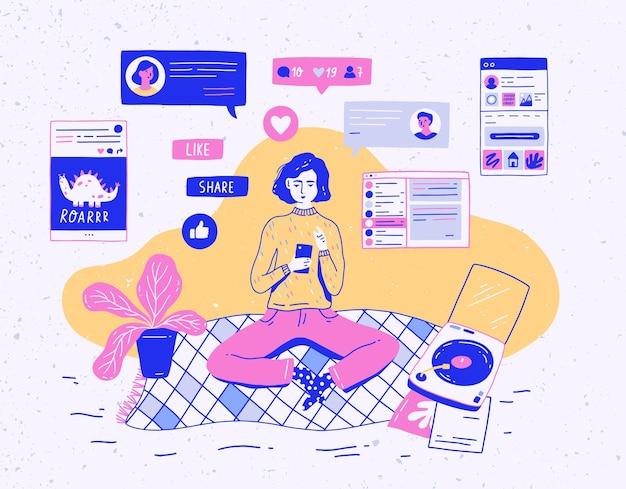 Dziewczyna siedzi w domu, trzyma telefon komórkowy i rozmawia lub otrzymuje informacje zwrotne w sieci społecznościowej