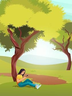Dziewczyna siedzi z telefonem komórkowym pod drzewem, wysyła wiadomości, czyta. krajobraz przyrody
