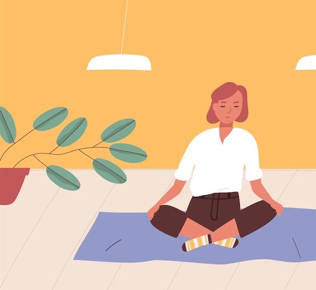 Dziewczyna siedzi ze skrzyżowanymi nogami na podłodze i medytuje.