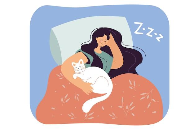 Dziewczyna śpi w łóżku z białym kotem