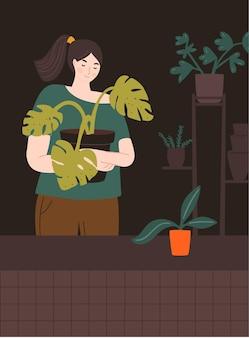 Dziewczyna trzyma duży garnek z rośliną monstera domowy ogrodnik w pokoju ze stojakiem na rośliny