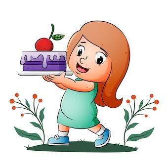 Dziewczyna trzyma i pokazuje ciasto z kremem i dużą wisienką ilustracji